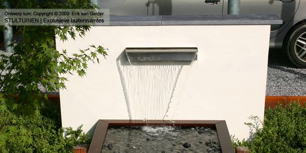 Witte tuinmuur met waterval in moderne tuin
