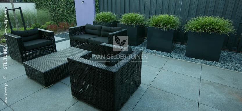 Moderne lounge tuin met grote tegels en plantenbakken
