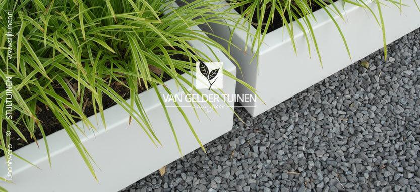 Grote witte plantenbakken in moderne tuin met antraciet split