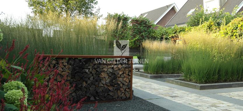 Houtopslag van cortenstaal in moderne tuin