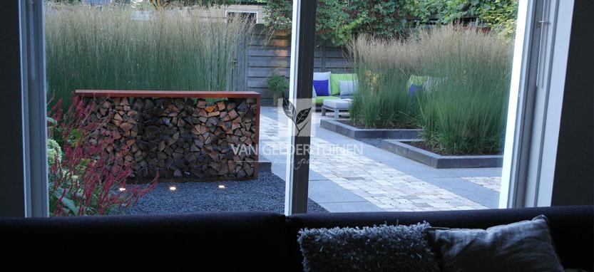 Zicht vanuit woning moderne strakke tuin met siergrassen