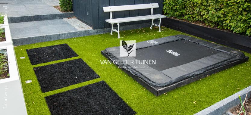 Tuin met hoogteverschil, kunstgras en trampoline