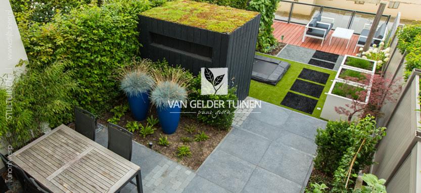 Moderne kindvriendelijke onderhoudsarme tuin met grote tegels en aluminium plantenbakken, kunstgras en trampoline