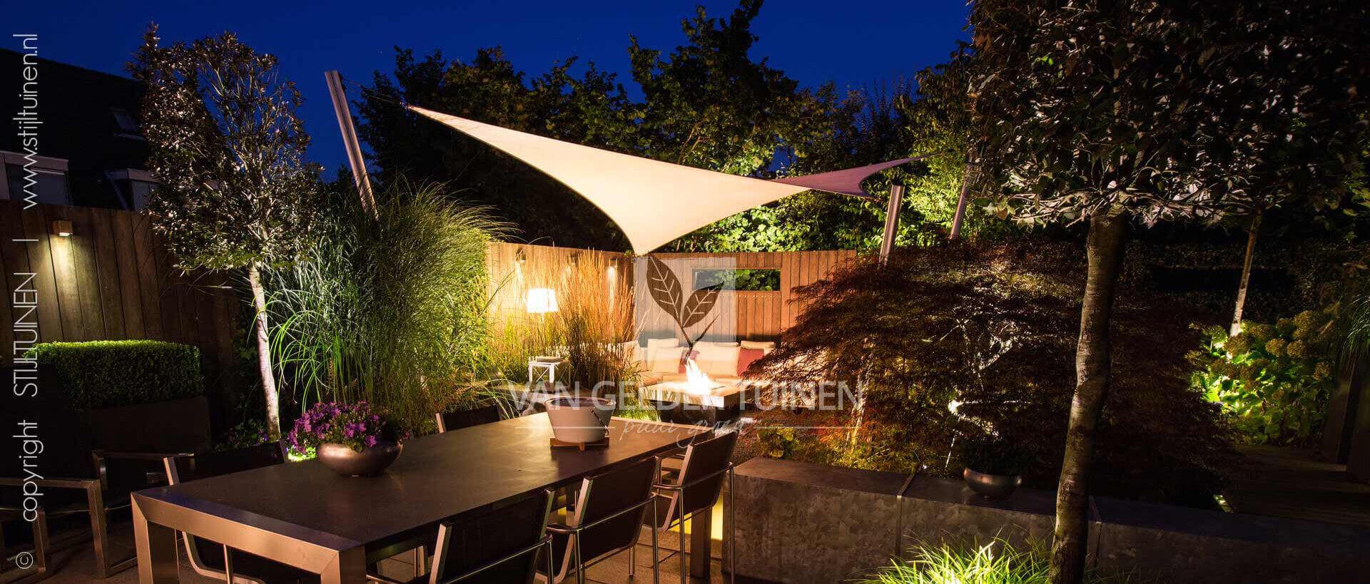 Sfeervolle tuin in avondlicht. Ontwerp door Van Gelder Tuinen